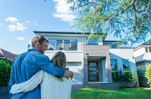 Couple standing in front of their new home. They are both wearing casual clothes and embracing. Rear view from behind them. The house is contemporary with a brick facade, driveway, balcony and a green lawn. The front door is also visible. Copy space